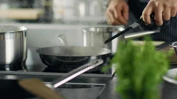 Profesionální kuchař vaří Flambe stylu. Připravuje jídlo v pánvi s otevřenou Flames.He prací v moderní kuchyni s různými přísadami povalovat.