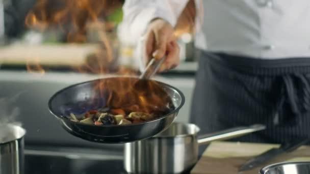Profesionální kuchař vaří Flambe stylu. Připravuje jídlo v misce s otevřeným ohněm. Pracuje v moderní kuchyni s různými přísadami povalovat.