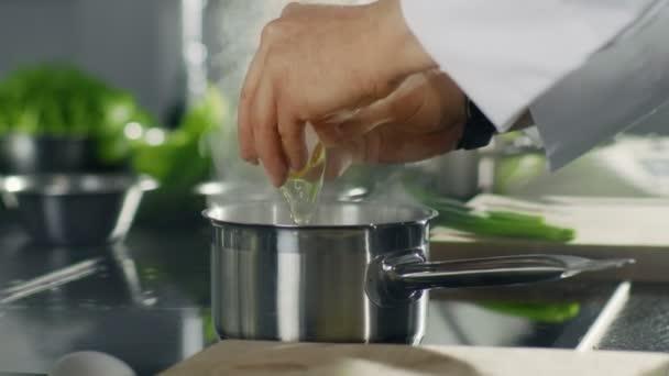 Detail z hrnce na vařič, když kuchař vejce do varné misky. Nerezové kuchyňské vypadá moderní