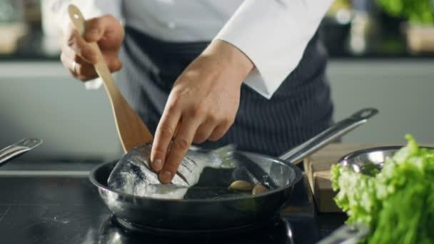 Slavný šéfkuchař restaurace otočí ryb na horkou pánev. Close-up Shot pan s malebnými zeleniny rozebírané.