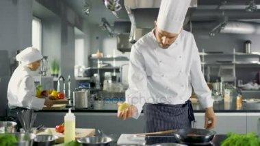 Profesionální kuchař ždímá citronová šťáva na rozpálené pánvi s červenou rybí filé na něm. Pracuje v moderní kuchyni.