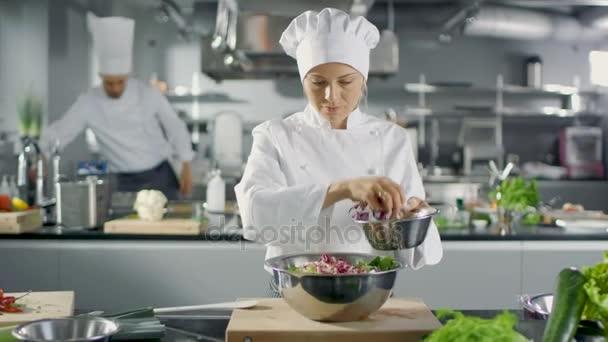 V známé restauraci ženské kuchař připraví salát. Pracuje ve velké moderní kuchyni