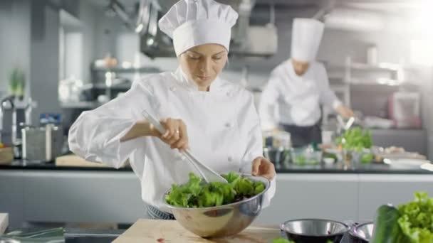 Női szakács egy híres étterem készíti saláta. Ő dolgozik egy nagy Modern konyha.