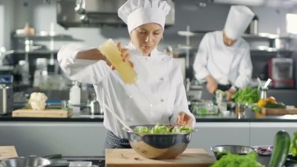 in einem berühmten Restaurant kocht Köchin bereitet Salat, Anzeigen Öl. sie arbeitet in einer großen modernen Küche.