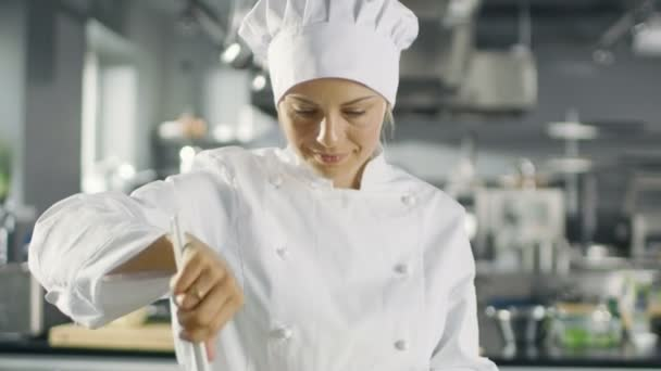 Ve známé restauraci žena šéfkuchař připravuje salát. Pracuje ve velké moderní kuchyni.