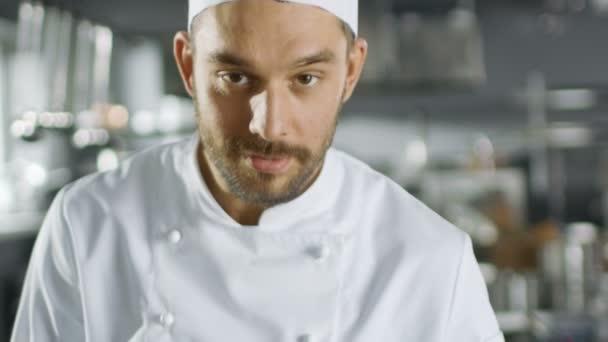 Portrét z pohledný mladý kuchař na fotoaparátu v pomalém pohybu. Mělká Hloubka pole záběru