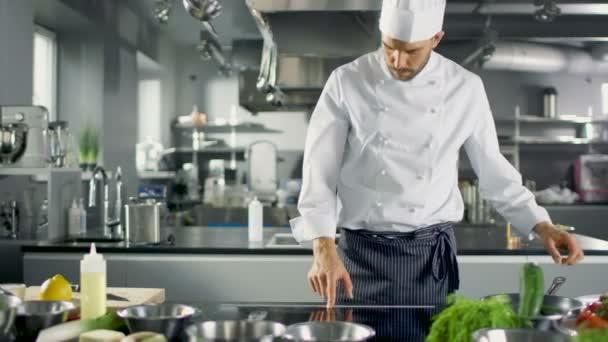 professioneller Koch, der in einer berühmten Restaurantküche arbeitet. beginnt mit der Zubereitung seines Spezialgerichts, schaltet den Herd ein und stellt eine Pfanne mit Öl darauf.