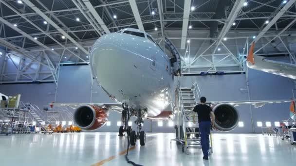 Značka nové letadlo stojící v hangáru údržby letadel během údržby letadel inženýr / technik / mechanik jde uvnitř kabiny přes žebřík / rampa.