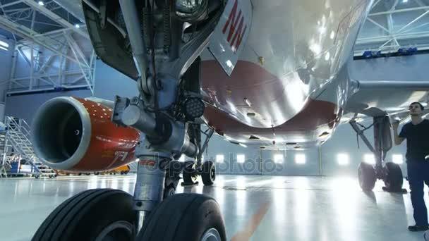 V hangáru údržby letadel inženýr / technik / mechanik vizuálně kontroluje letadla podvozek a tělo/trup chůze pod to.