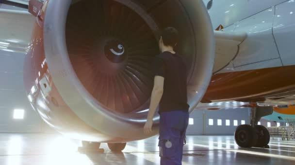 V hangáru technik údržby letadel / technika / mechanik kontroluje s baterkou letadlo proudovým motorem.