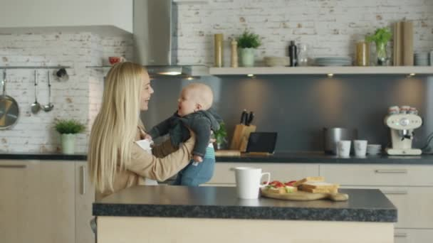 Young Mother Nursing Her Laughing Child while Standing on the Kitchen.