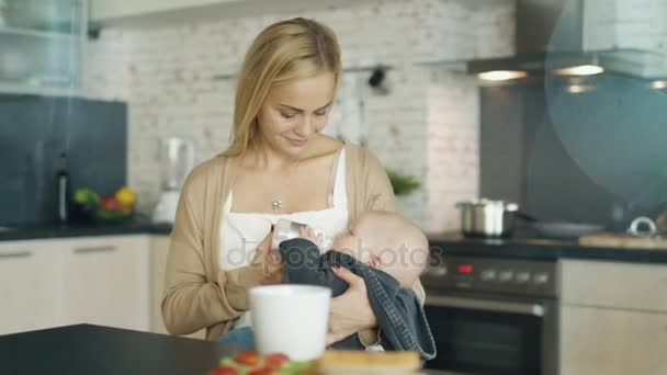 Beautiful Young Mother Feed Her Cute Child from a Bottle. All this is Happening on a Modern Kitchen.