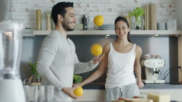 Zpomaleně chlap imponoval jeho dáma s žonglováním pomeranče v kuchyni