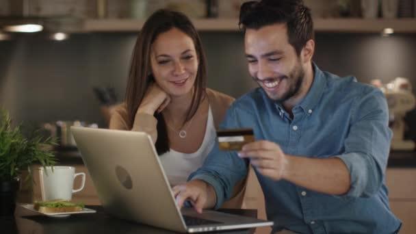 Boldog pár használ Laptop, Internet-vásárlások, jóképű férfi hiteletek kártya a kezében