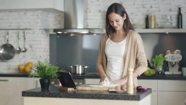 Mladá dívka připravuje mouky na vaření. Pro recept referenční Tablet stojí na kuchyňském stole. Pohledný podnikatel přítel přijde k ní a objetí. Jak úsměv