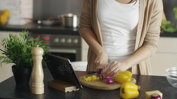 Detail žena krájení zeleniny na dřevěné desce. Poradenství její tabletový počítač za recept.