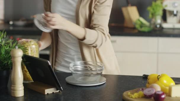 Nahaufnahme einer jungen Frau, die eine Schüssel Pasta auf einer Küchenwaage misst. Sie verweist auf Tablet-Computer als Rezept.