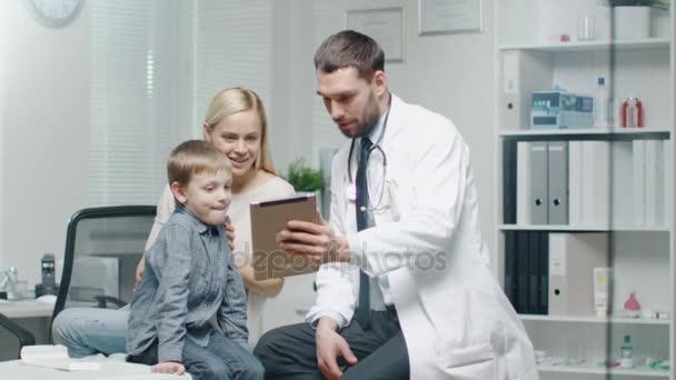 Der Arzt berät den kleinen Jungen und seine Mutter mit Hilfe einer Tablette. sie lächeln alle.