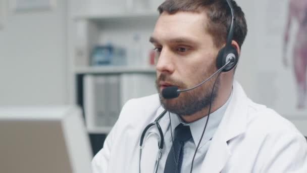 Der Arzt berät Patienten im Internet. er sitzt vor seinem PC und trägt Mikrofon.