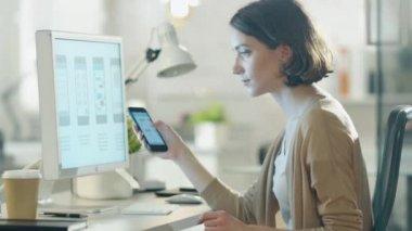 Krásné Burnette srovnává její obrazovka Smartphone s její ploše obrazovky počítače. Všechny děje v moderní a lehký úřadu