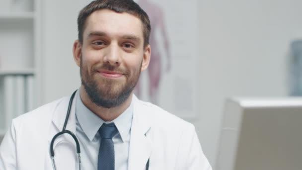 Großaufnahme eines männlichen Arztes an seinem Schreibtisch. er unterbricht seine Arbeit und lächelt in die Kamera.