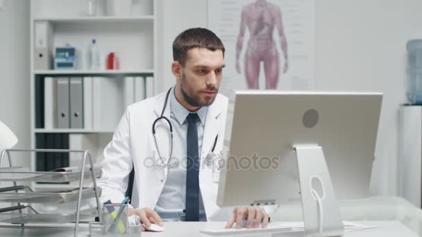Male Doctor is Working at His Desk. He Interrupts His Work, Folds His Hands and Smiles at the Camera.