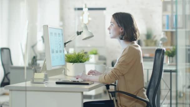 Creative brunetka pracuje na návrhu na její stolního počítače. Sedí v její vývojáře Office.