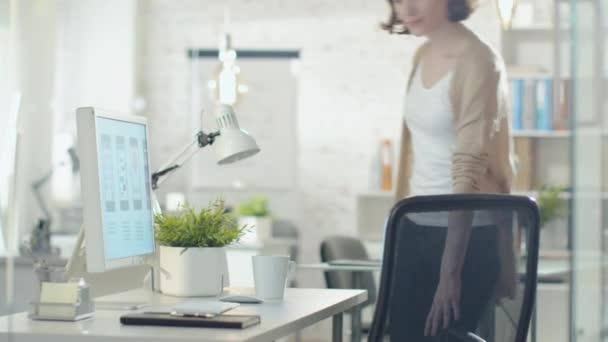schöne kreative Brünette kommt und sitzt an ihrem Desktop-Computer. beginnt mit der Arbeit am Design.