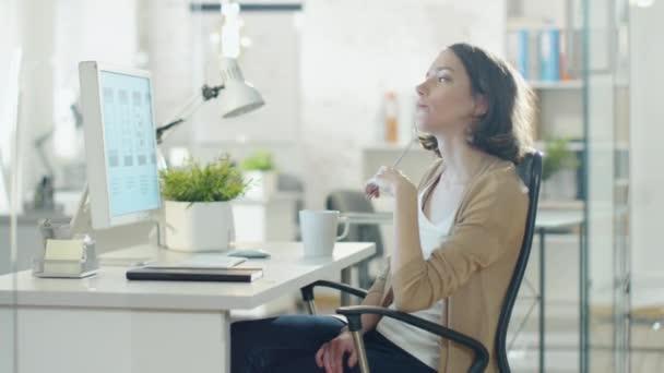 Zaměřená kreativní žena sedící u svého stolního počítače v kanceláři. Myslet na řešení problémů a kroužení v křesle