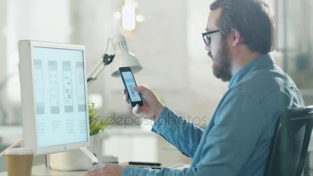 Mladá zaměřený člověk porovnává Smartphone a obsah plochy obrazovky. On sedí na jeho moderní kancelářské přístavby