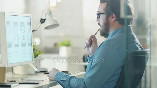 Zaměřil kreativní člověk si myslí, zatímco sedí na jeho pracovní stůl. Ten drží tužka a dívá se na ploše obrazovky počítače