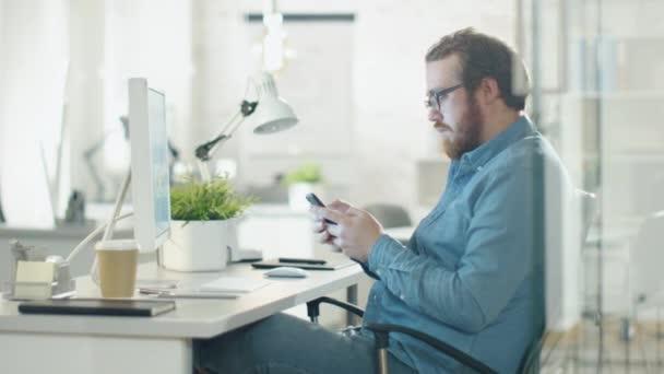 Kreativní člověk používá Smartphone, zatímco sedí na jeho pracovišti. Kancelář je lehký a moderní zelená rostlina na stůl