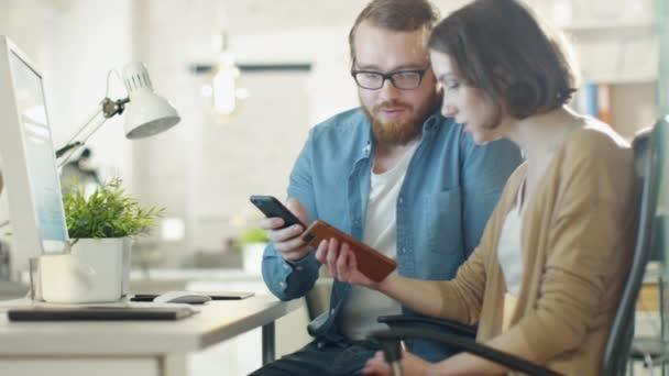 Mladý muž a krásná žena o práci problémů na pracovišti. Ona sedí u stolu. On stojí vedle ní. Mluví a přejděte na obrazovku
