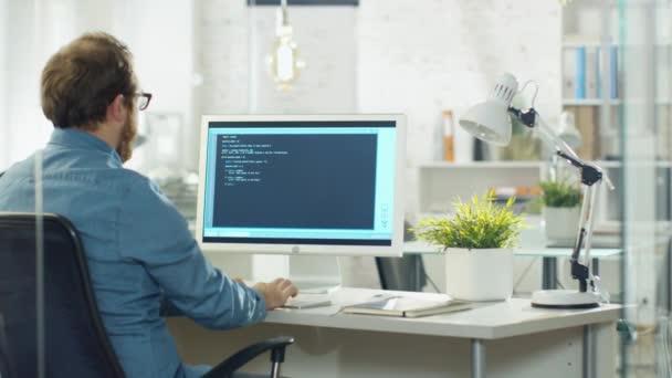 Jeunes barbus développeur écrit code sur son ordinateur de bureau