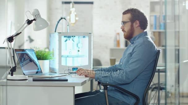 Junge bärtige Entwickler verwendet 3D-Drucker für die Modellierung. Er sitzt an seinem Schreibtisch in einem technologisch modernen Büro.