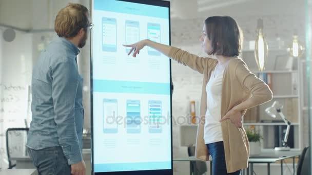 Mladí spolupracovníci o grafy, nakreslené na elektronické tabuli. Jejich kancelář je stylový a moderní hledá