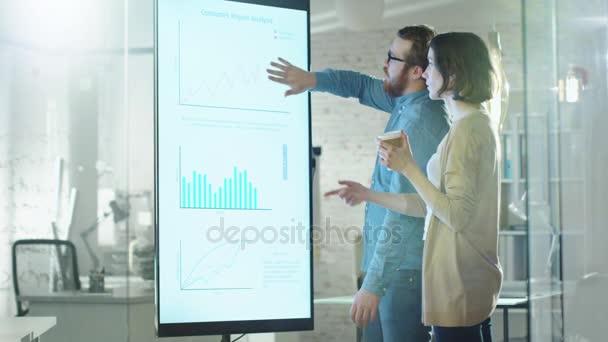 Mladý muž a žena o grafy, nakreslené na elektronické tabuli. Muž se zobrazí podrobnosti o obrazovky žena naslouchá držící šálek kávy v její kanceláři Hands.Their je stylový a moderní hledá