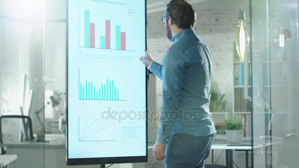 Mladý muž, práce s grafy na jeho elektronické tabule. Spolupracuje s tabuli. Jeho kancelář je jasně osvětlená a moderní hledá