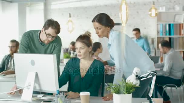 Young  Man and Two Women Stand before Computer Desk in a Creative Office. They Discuss Business Issues. Diverse People Working in Background.