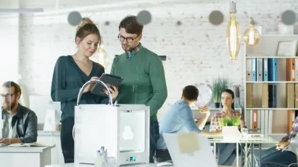 Krásná kreativní dívka ukazuje tabletový počítač k její stylový mužský kolega. Vyhledat v úřadu práce kreativní Loft s mladými lidmi v pozadí.