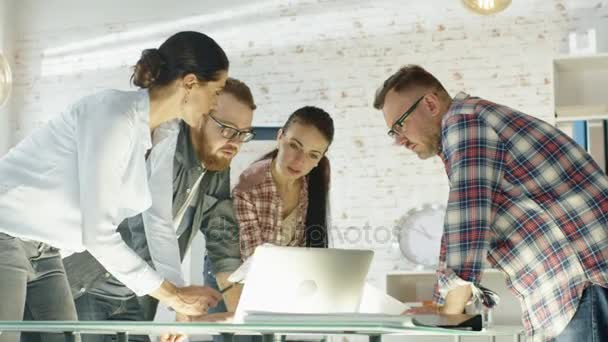V kreativní kancelář produktivní spolupracovníky kolem tabulky, s strategické plánování relace. Pracují na notebooky, výměnu poznámek a myšlenek.
