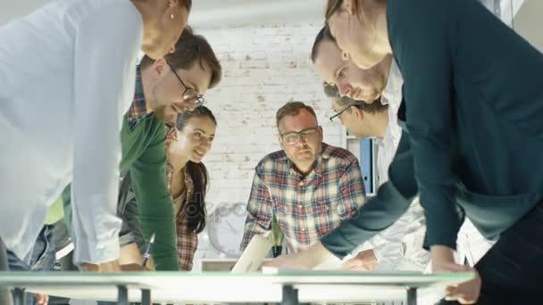im Kreativbüro stehen produktive Mitarbeiter mit strategischen Planungssitzungen am Tisch. Sie arbeiten an Laptops, tauschen Notizen und Ideen aus.