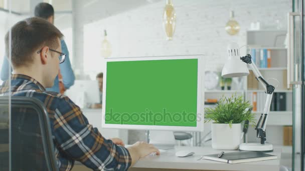 Close Up Of A Man Sitting At His Desk With Green Screen Pc On The