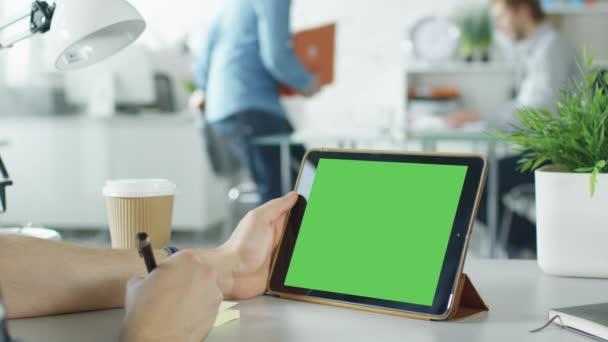 Detail lidské ruce držící fabion tabletový počítač a dělala si poznámky na lepící papír. V pozadí světlé moderní kanceláři s lidé pracují v ní