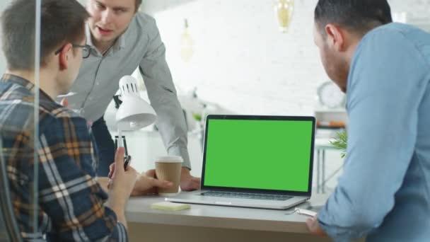 Tři kreativní muži projednání obchodní kolem zelené vytříděné Laptop. Jsou to světlé moderní kancelář.