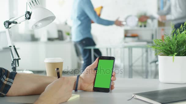 A férfi keze gazdaság zöld képernyő Smartphone és így veszi tudomásul, öntapadó papír toll részlete. A háttér világos Modern irodában két férfi kezet rázott, és kezdődik a beszélgetés