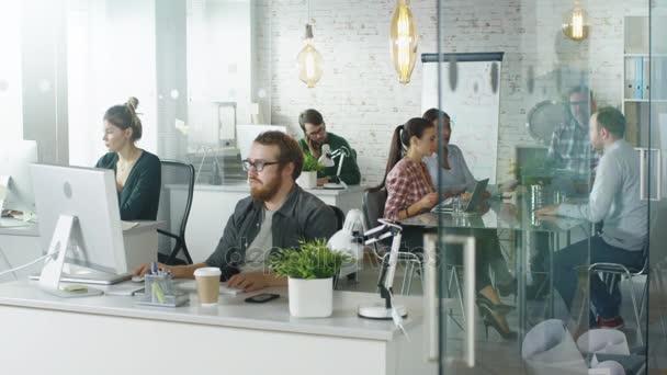 Wochentag in einem geschäftigen Kreativbüro. Büromenschen, die an ihren PCs arbeiten und telefonieren. Mann gesellt sich zu Kollegen am Konferenztisch, an dem geschäftliche Diskussionen stattfinden.