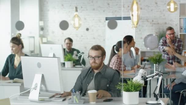 Wochentag in einem geschäftigen Kreativbüro. Büromenschen, die an ihren PCs arbeiten und telefonieren. Mann gesellt sich zu Mitarbeitern am Konferenztisch, wo geschäftliche Gespräche stattfinden.