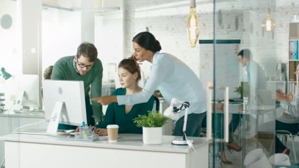 A fényesen kivilágított és Modern kreatív iroda. Előtérben három ember vitasd meg üzleti asztali számítógépet használ. A háttér csoport munkatársai munkáját megvitassák kapcsolatos ügyekben.