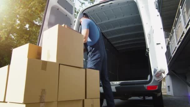 Dodávky muž zatížení lepenkových krabic do své dodávky. Zpomalený pohyb